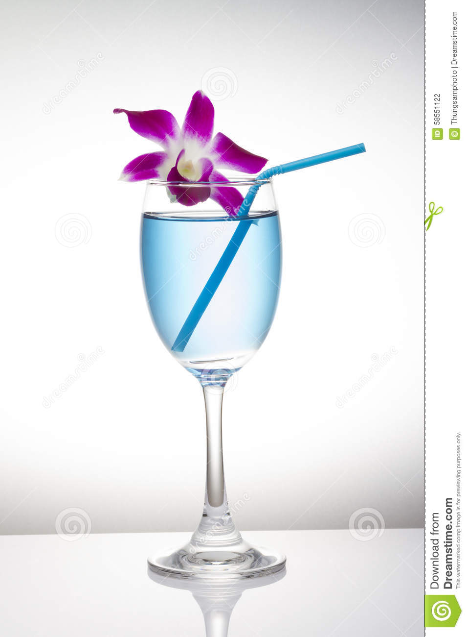Blue cocktail in wine glass and orchid flower on white background