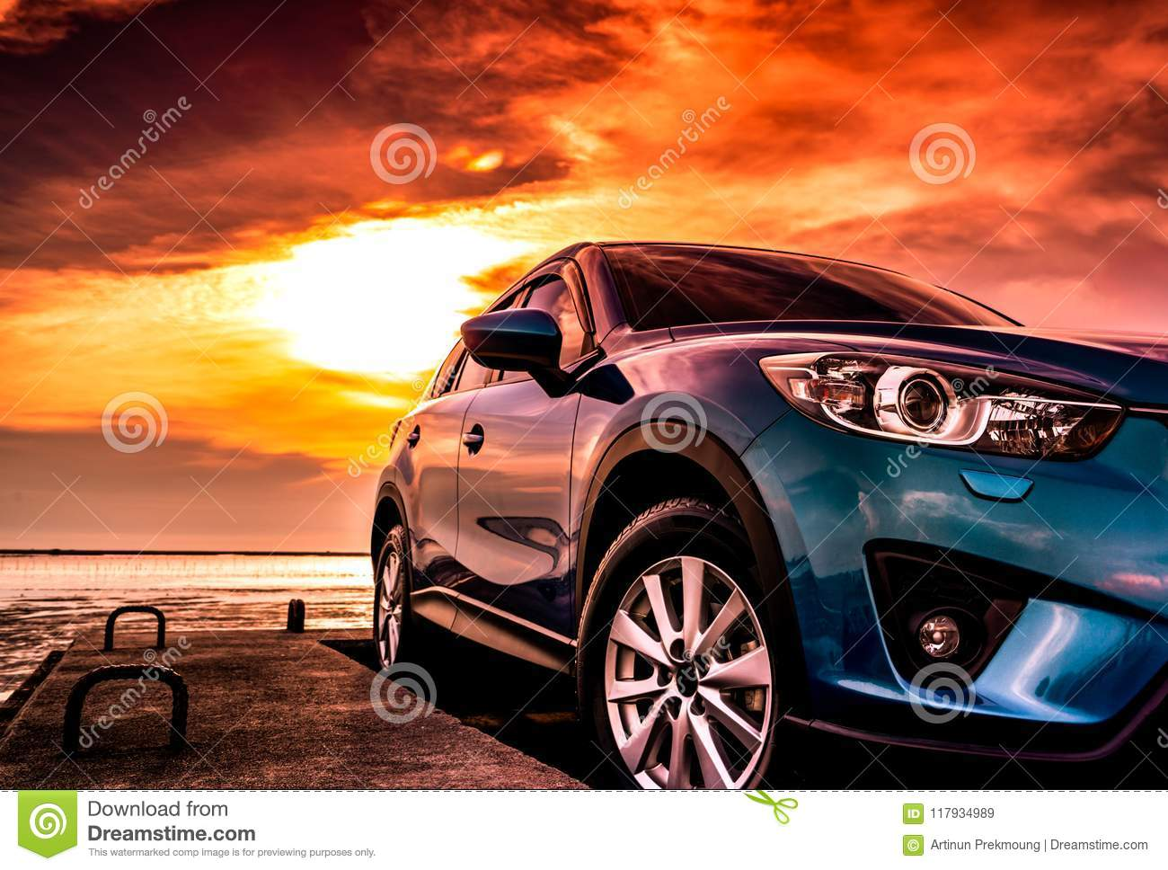 Blue compact SUV car with sport, modern, and luxury design parked on concrete road by the sea at sunset. Front view of beautiful