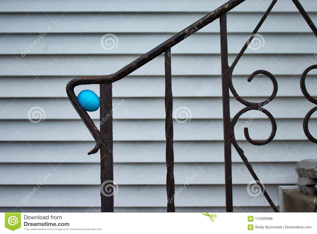 Blue dyed Easter egg, hidden for an egg hunt, in crook of fence railing on concrete stairs of midwestern home.