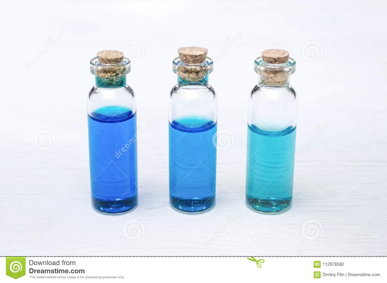 Blue essence oil tincture on white wooden background.