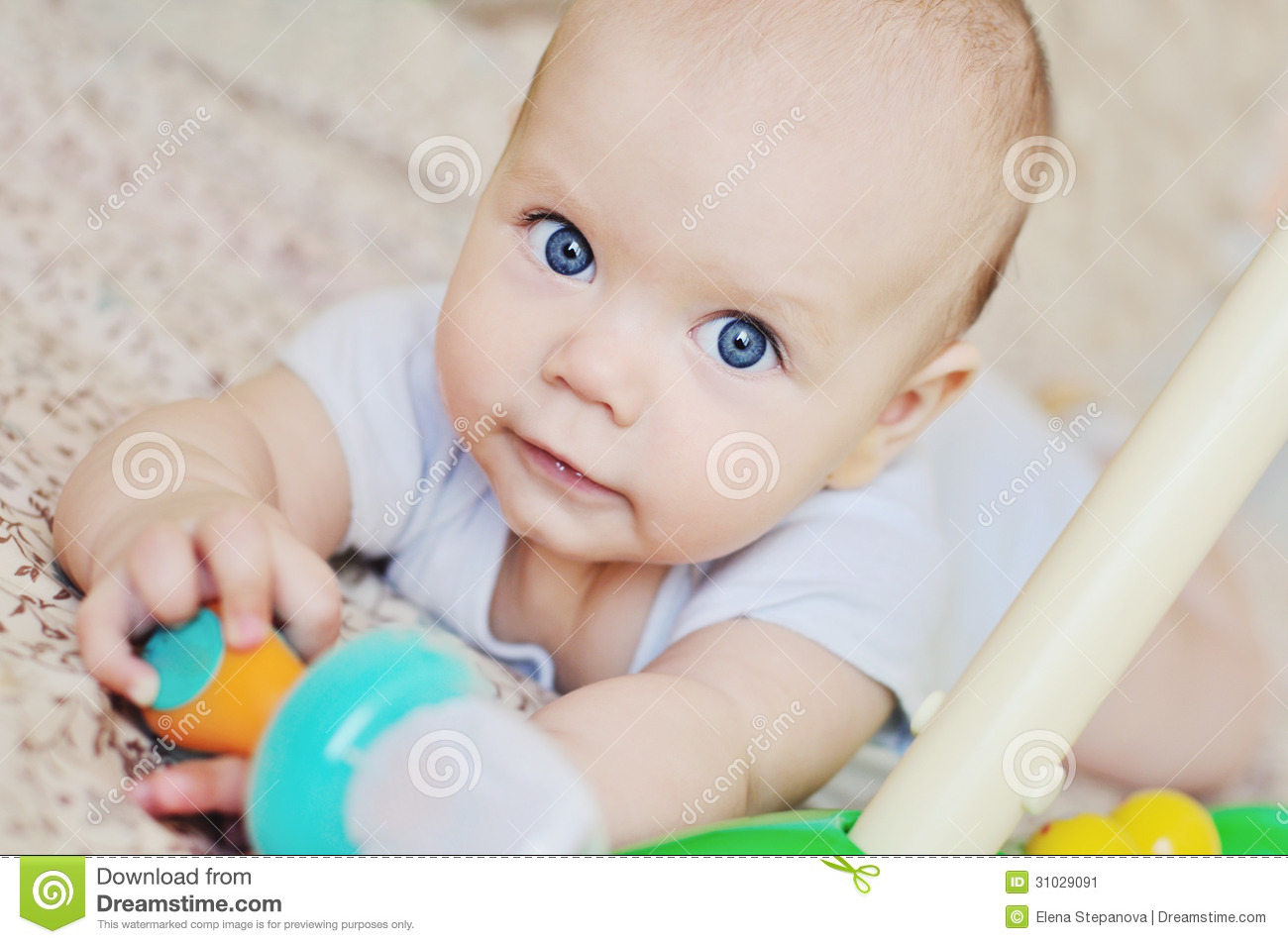 Blue eyed baby with toys