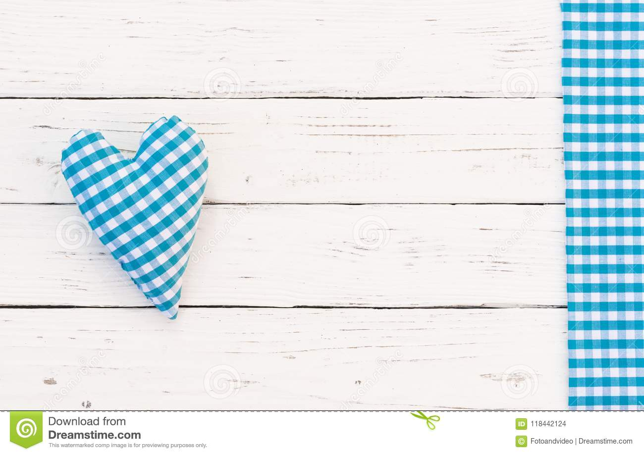 Blue fabric heart on white wood with blue checked border