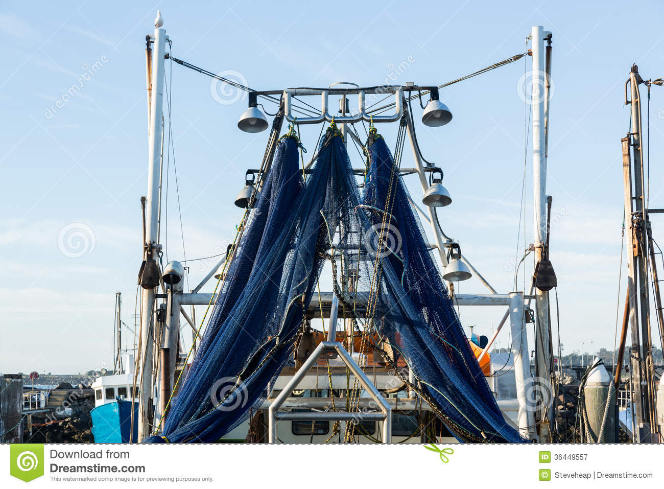 Blue fishing nets or trawl hanging from ship stock image for How to ship fish