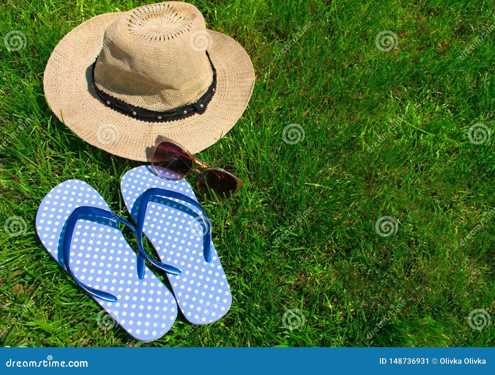 Blue flip flops and summer hat on green grass.