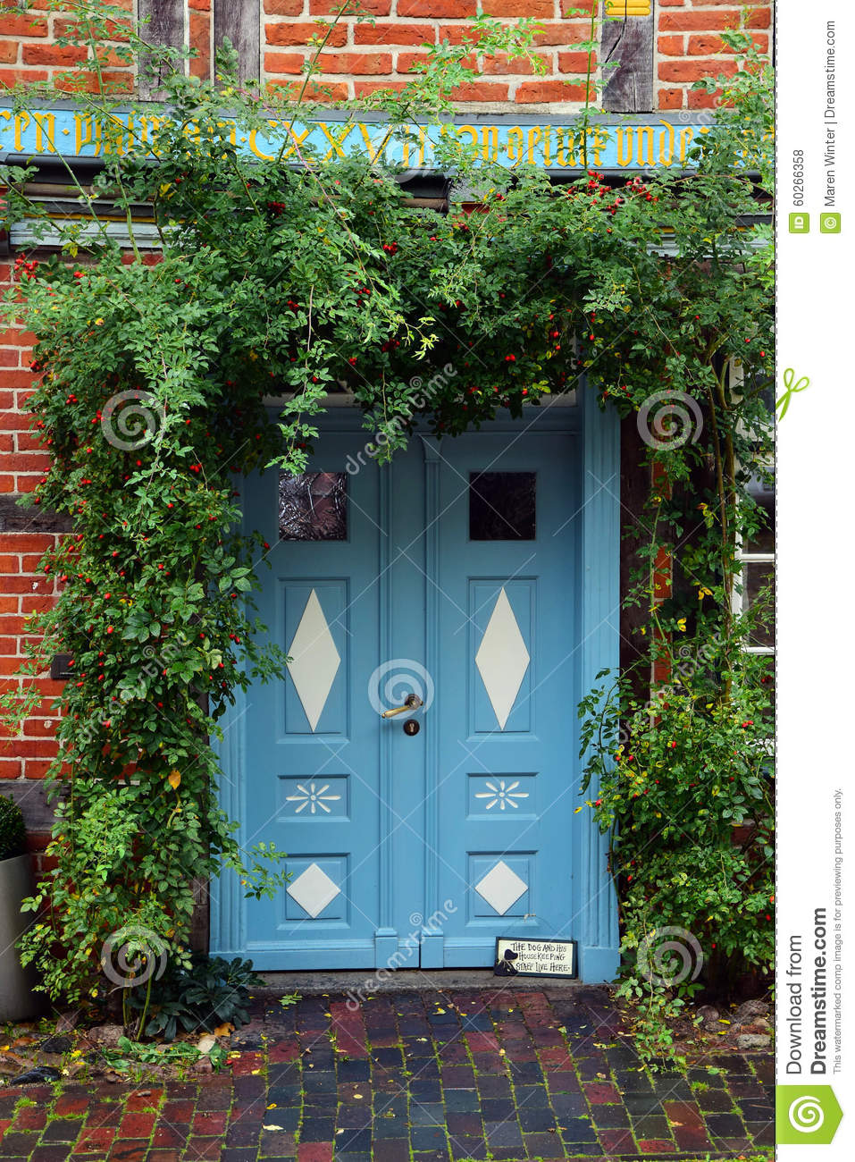 Blue Front Door In A Historic House With Climbing Plants