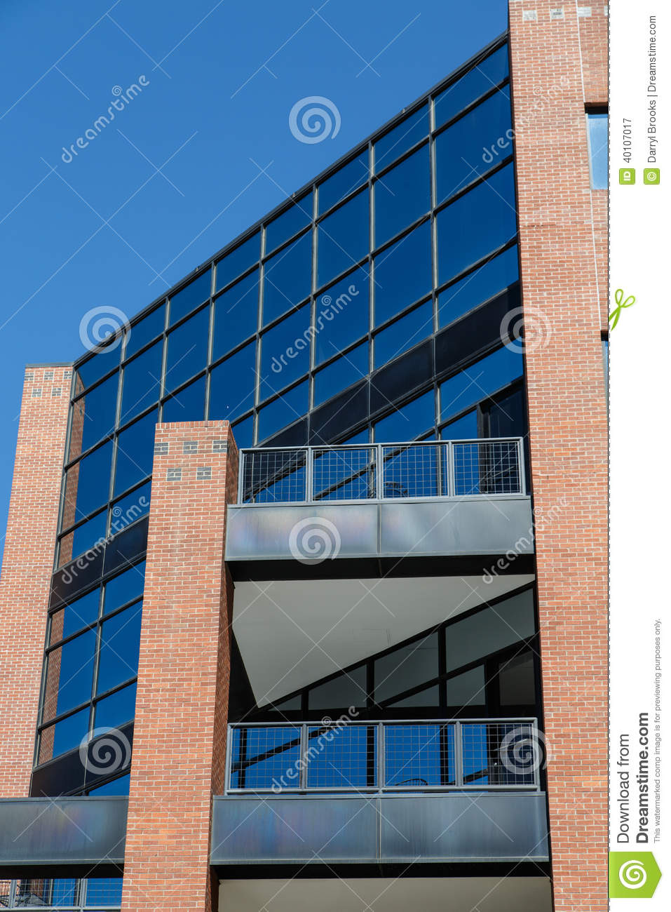 blue glass office tower with red brick columns stock photo