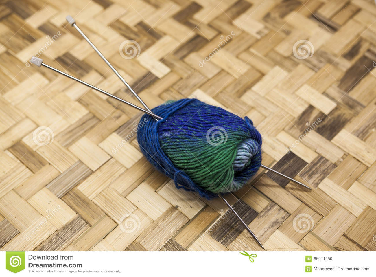 Blue green balls of yarn for knitting with spokes on a on a wooden background.