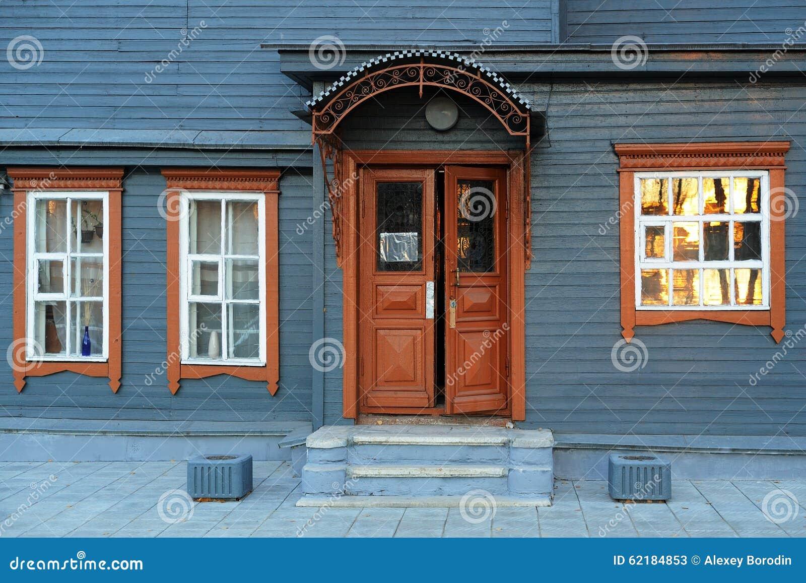 Blue grey wooden house facade with brown open door stock for Plan maison facade