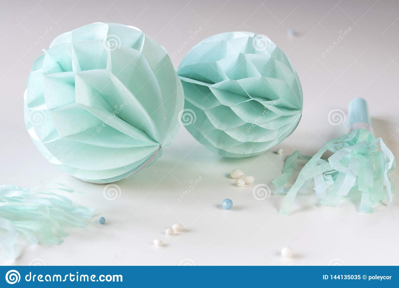 Blue honeycombs with paper trumpets on white table