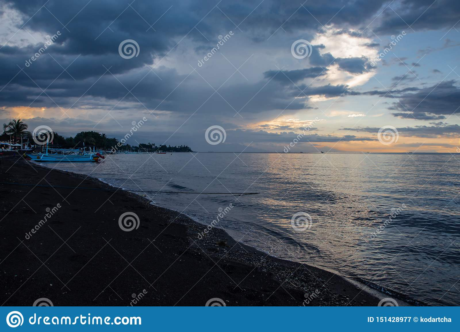 Blue hour over calm ocean and black sand beach with balinese boat