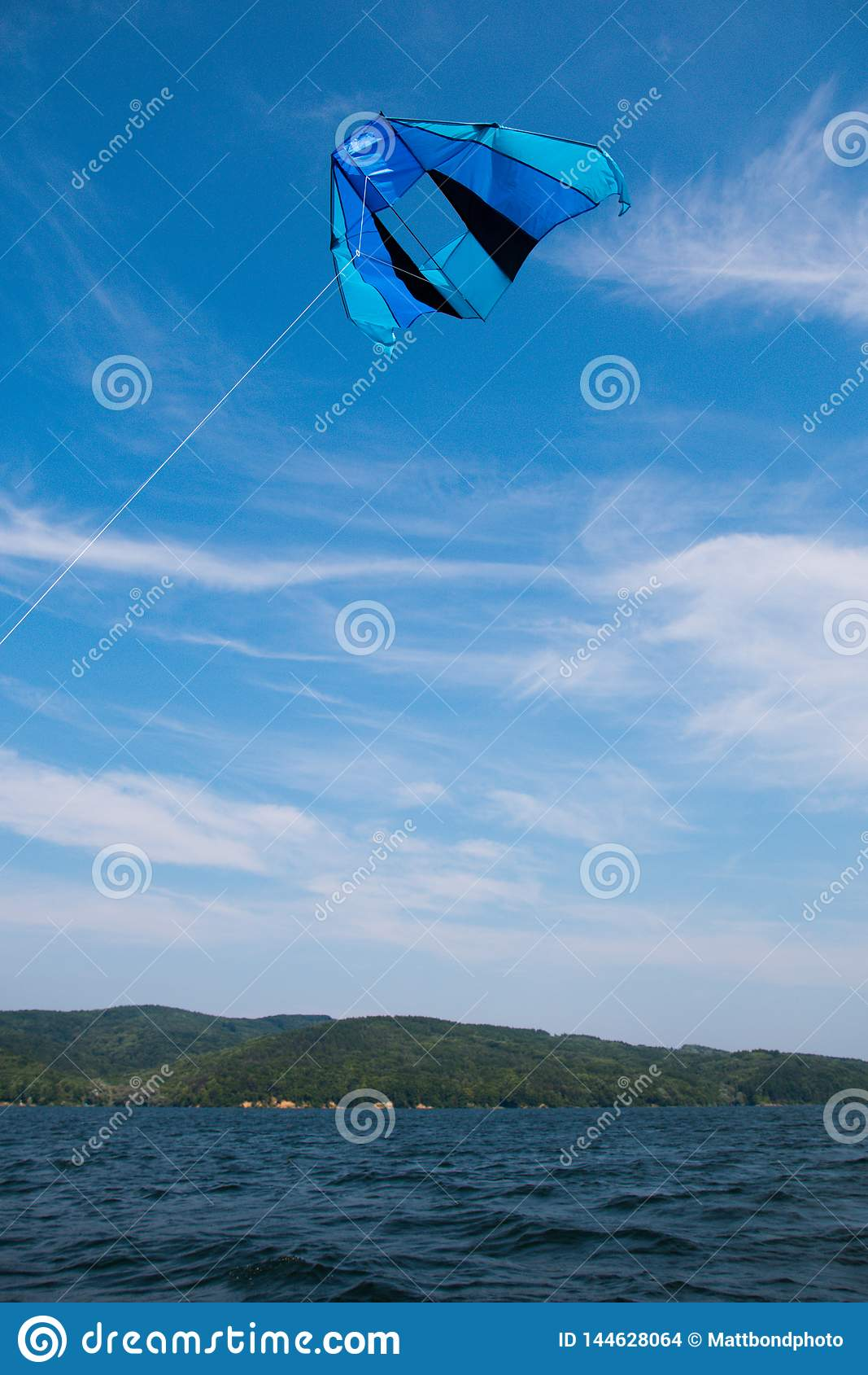 Blue kite on blue sky over water