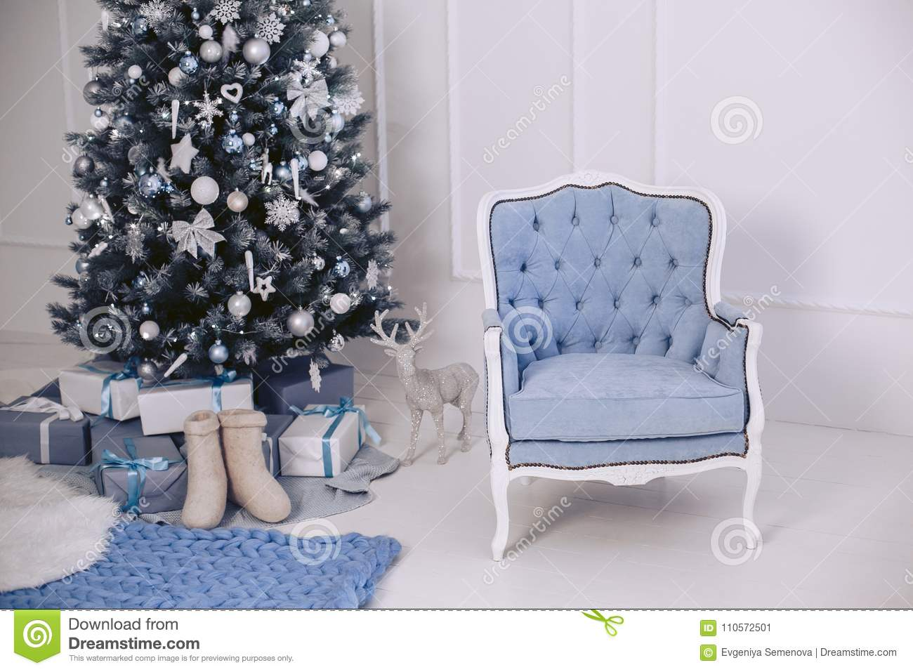 A blue modern elegant chair in the New Year`s interior. Christmas tree with decorations. Gifts in packages