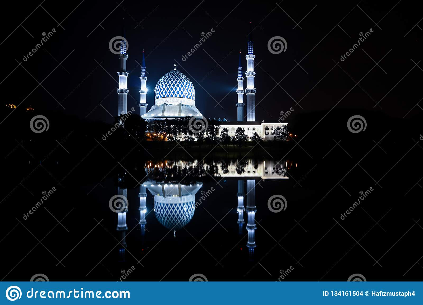 The blue mosque view during night time with reflection in the lake.