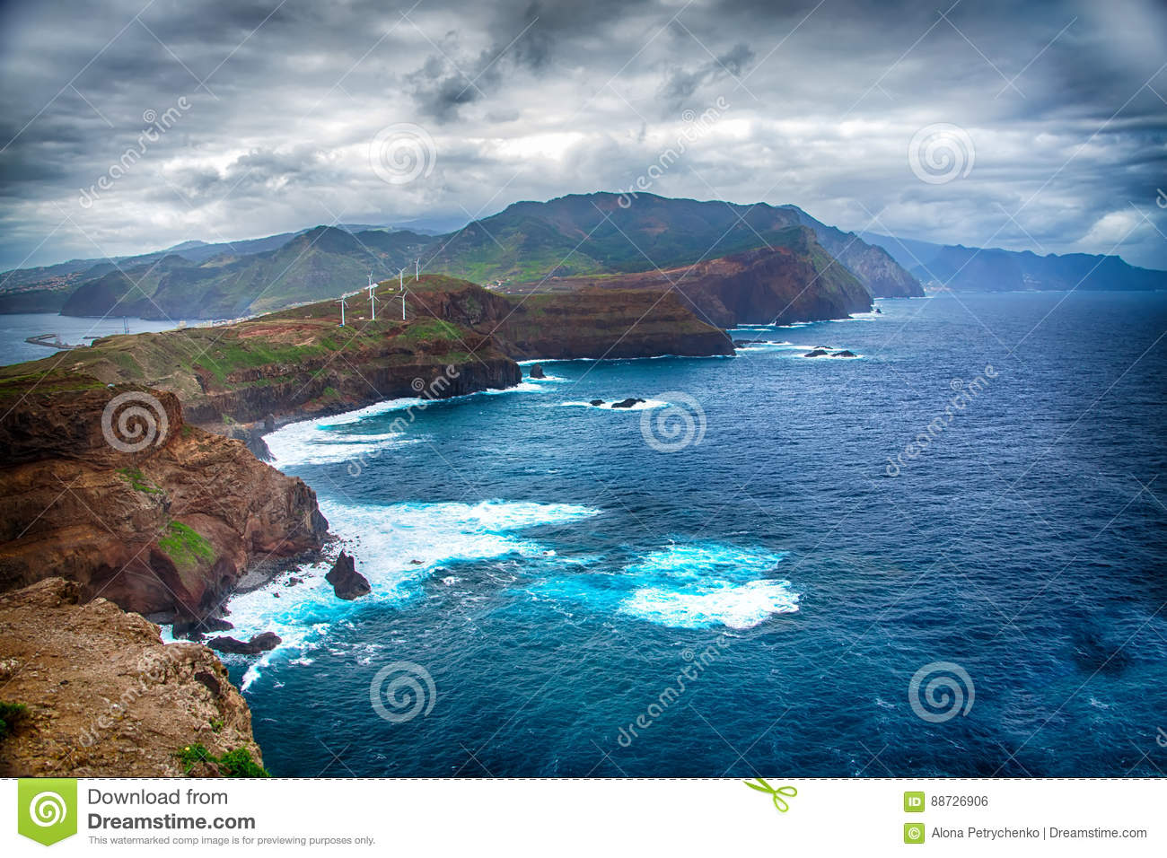 Blue ocean, mountains, rocks, windmills and cloudy sky