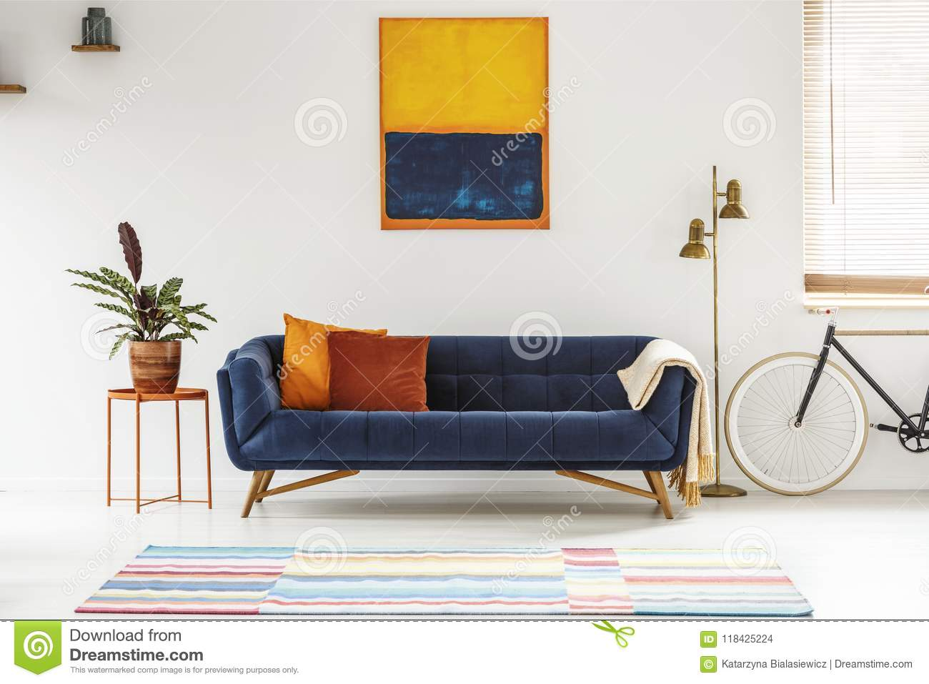 Blue And Orange Painting Hanging On A White Wall Above An Elegant