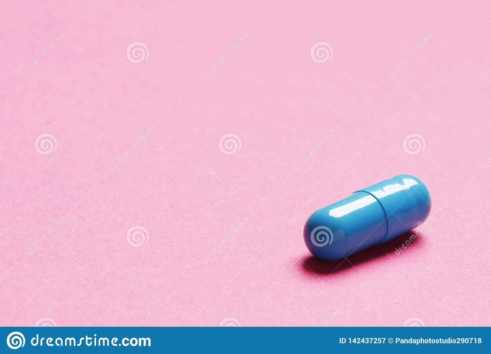 Blue pill on pink background