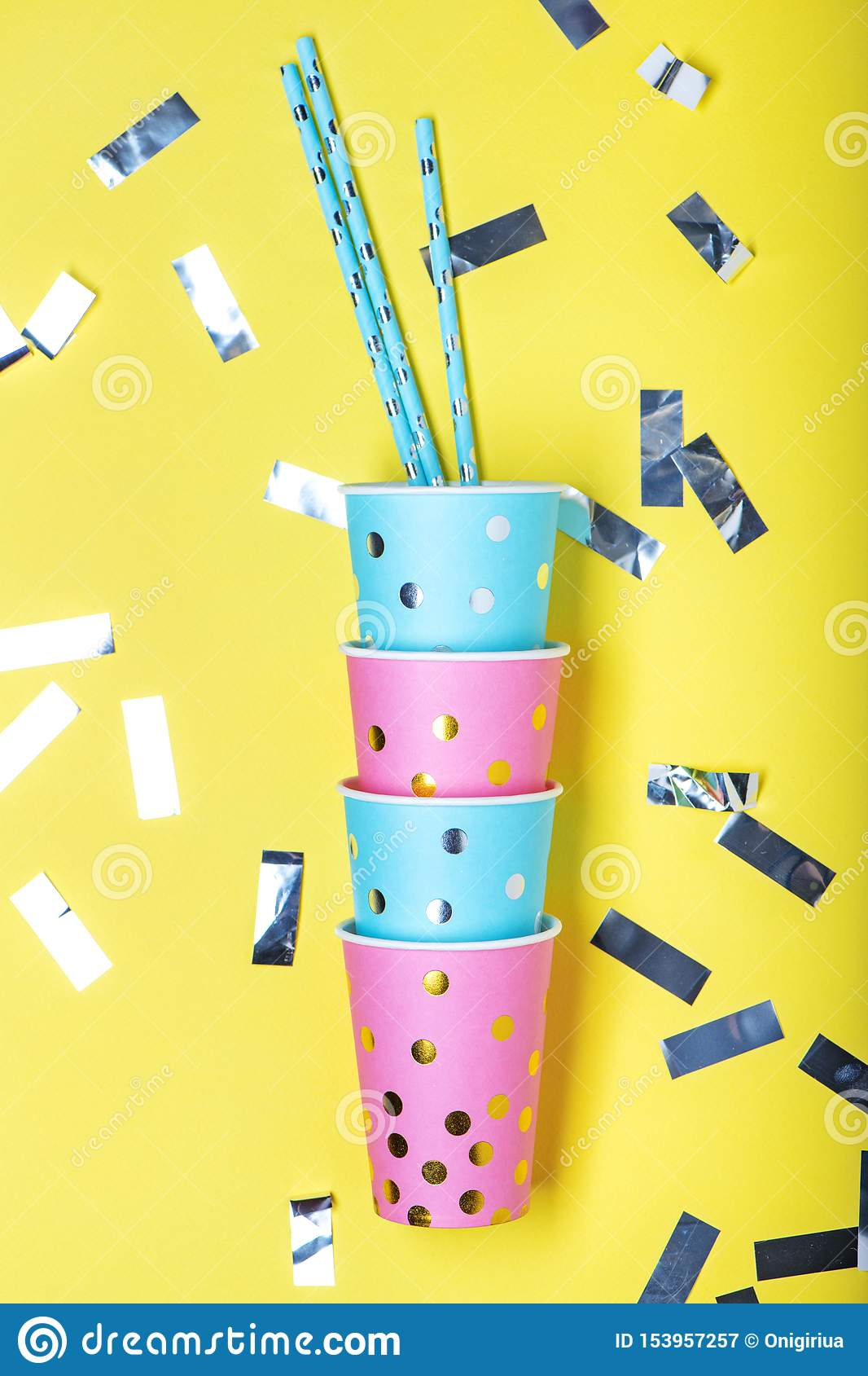 Blue and pink polka dot paper cups and straws on yellow background.