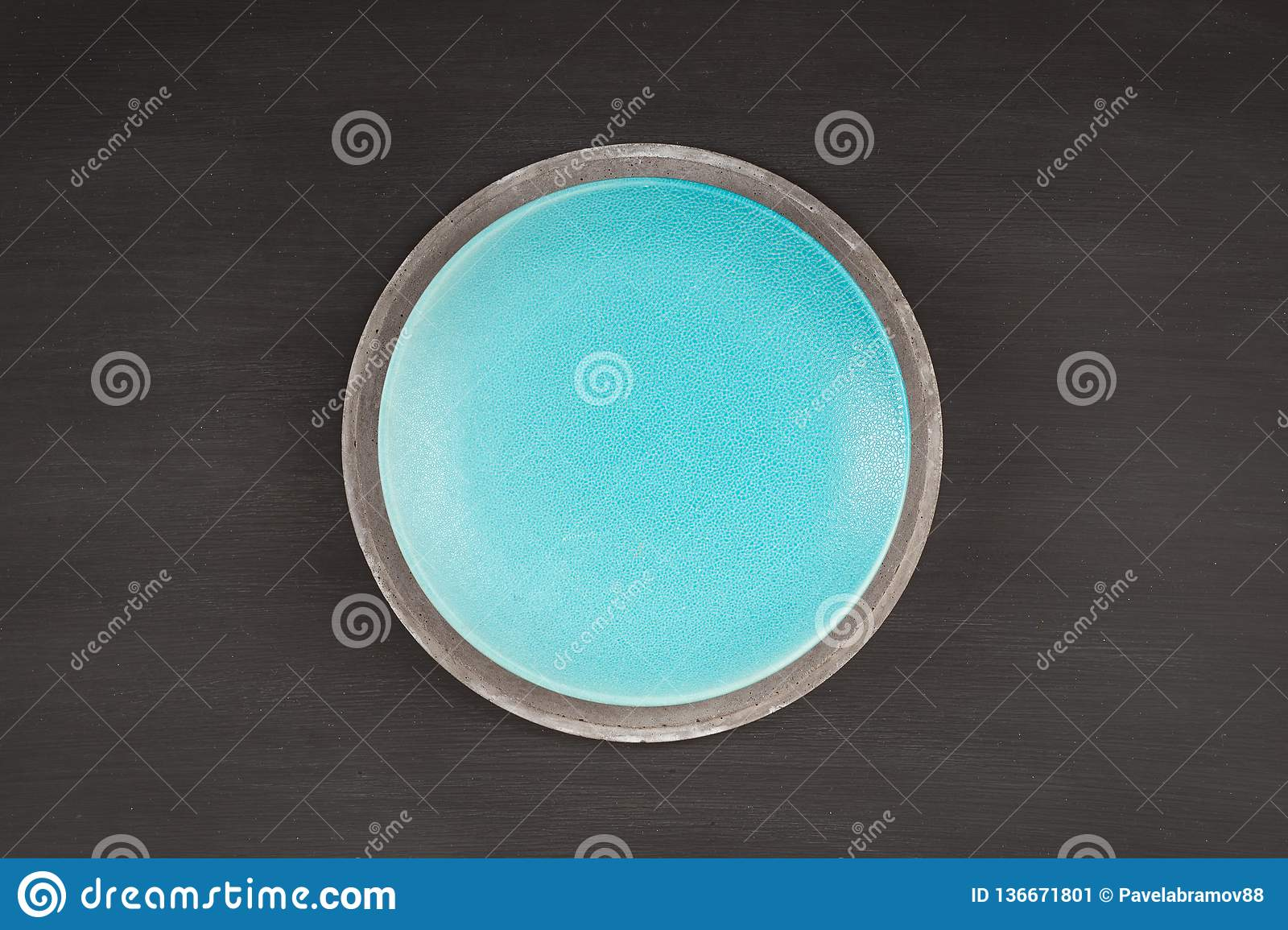 Blue plate on concrete plate on dark background