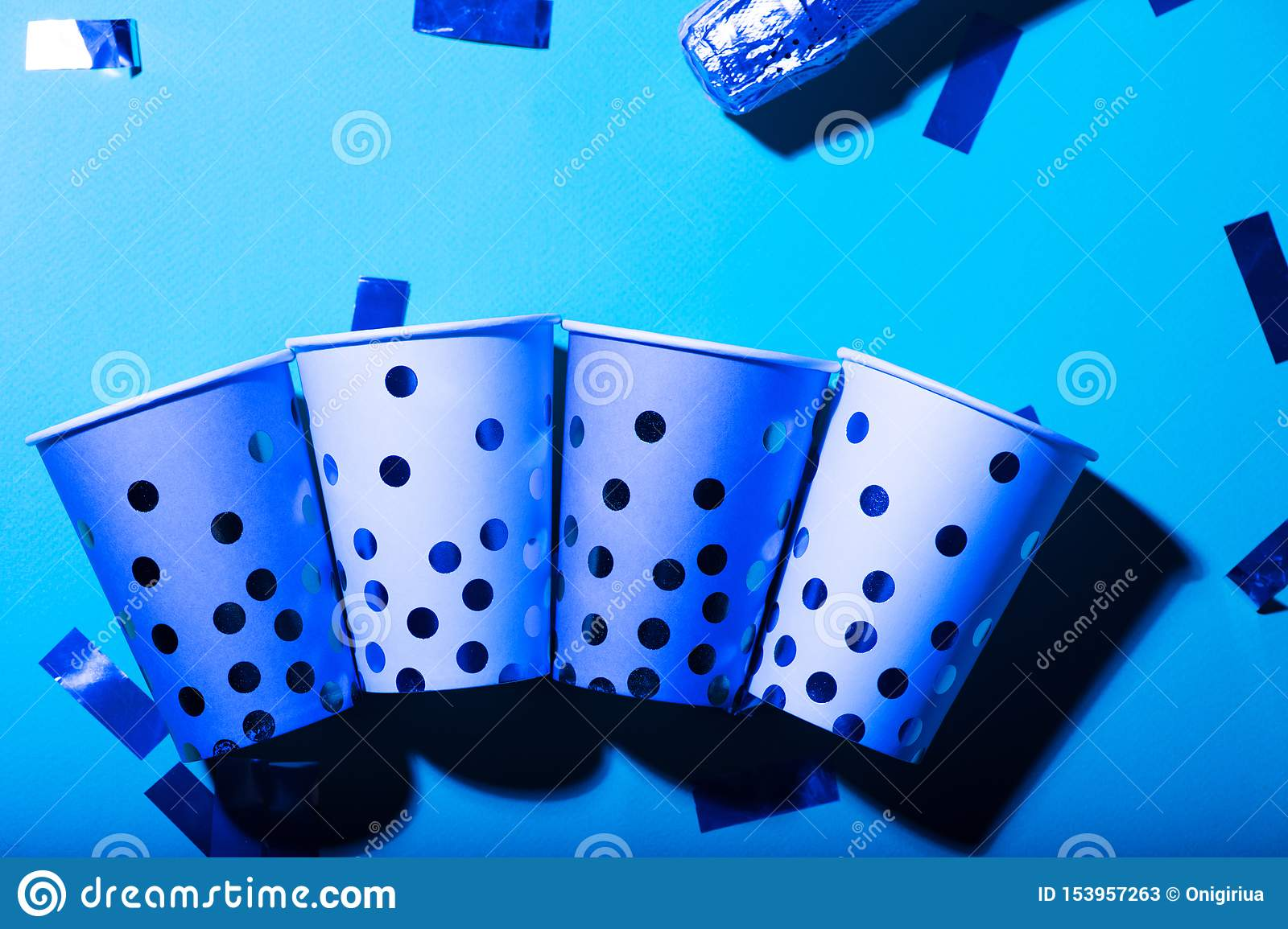 Blue polka dot paper cups and straws in ultraviolet light