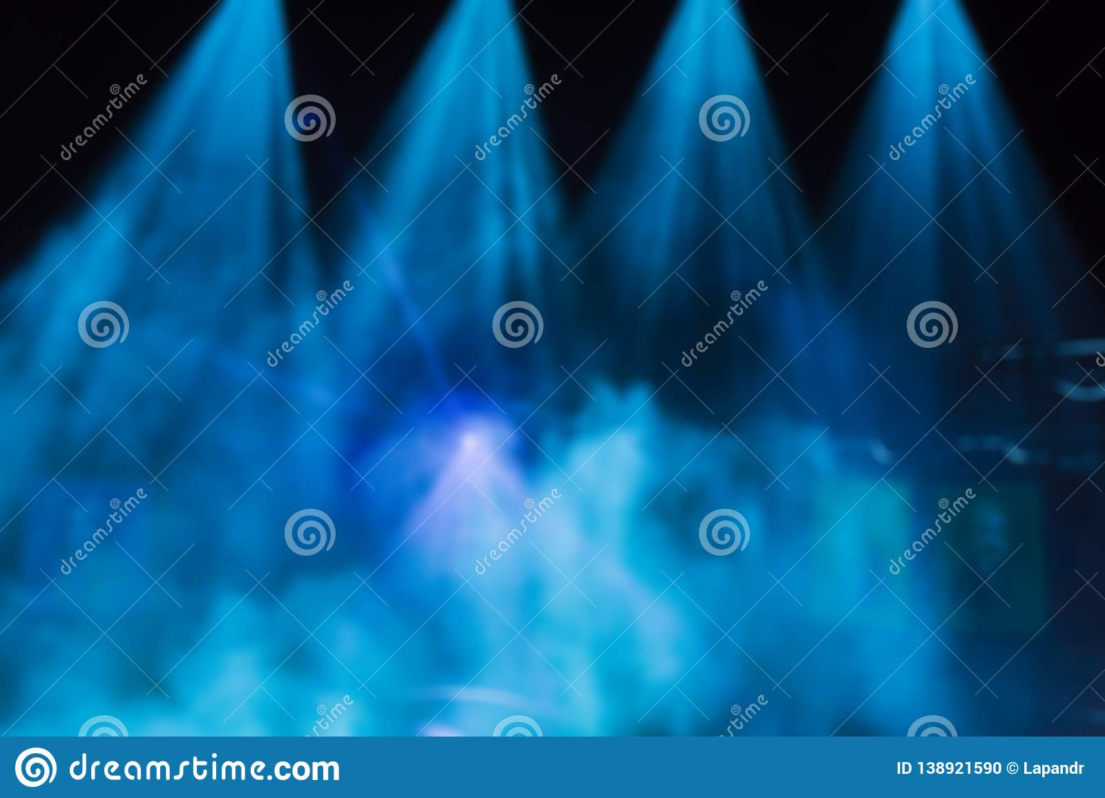 Blue rays of light from the spotlights through the smoke on the stage. Theatrical performance. Defocused abstract image