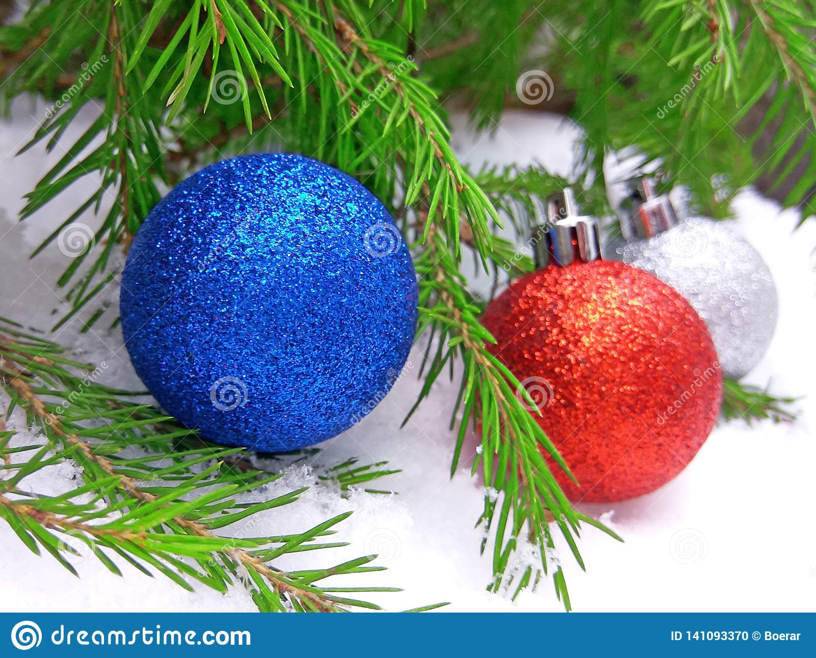 Blue, red and silver New Year balls with green fir tree on snowy background