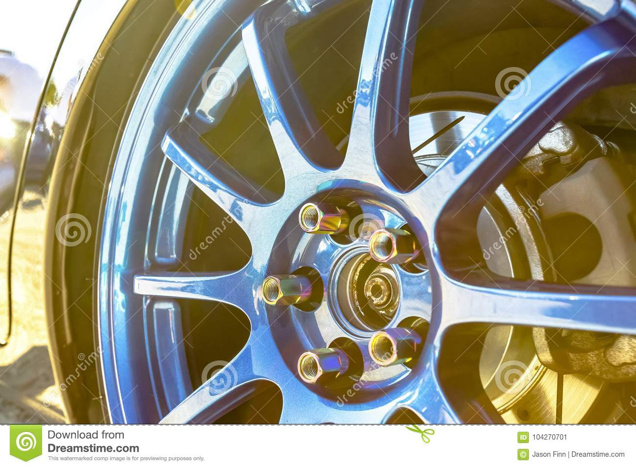 Blue Rims With Golden Bolts On A Black Reflective Car And Sun Bu