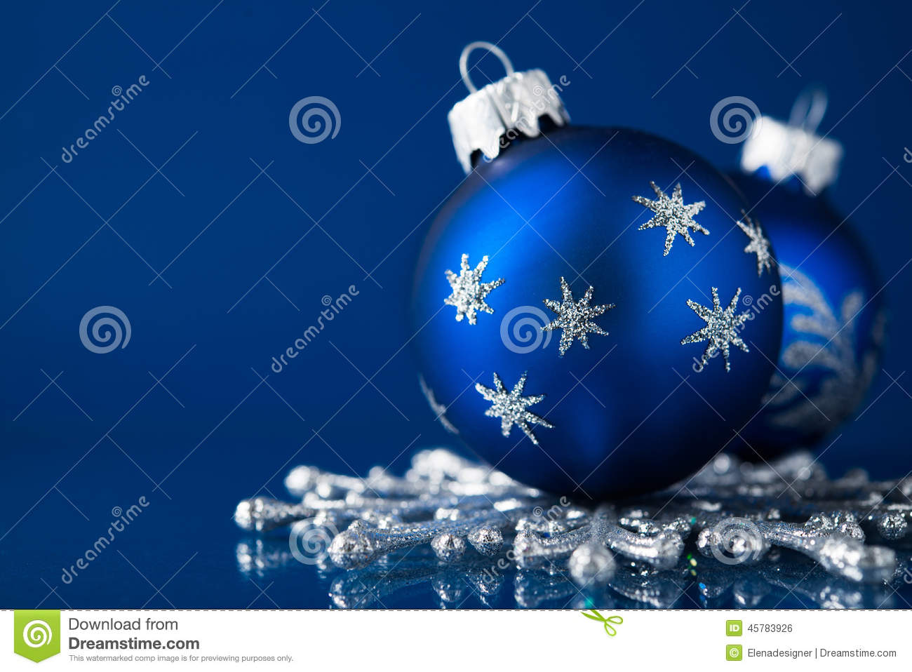 blue and silver christmas ornaments on dark blue background with space for text