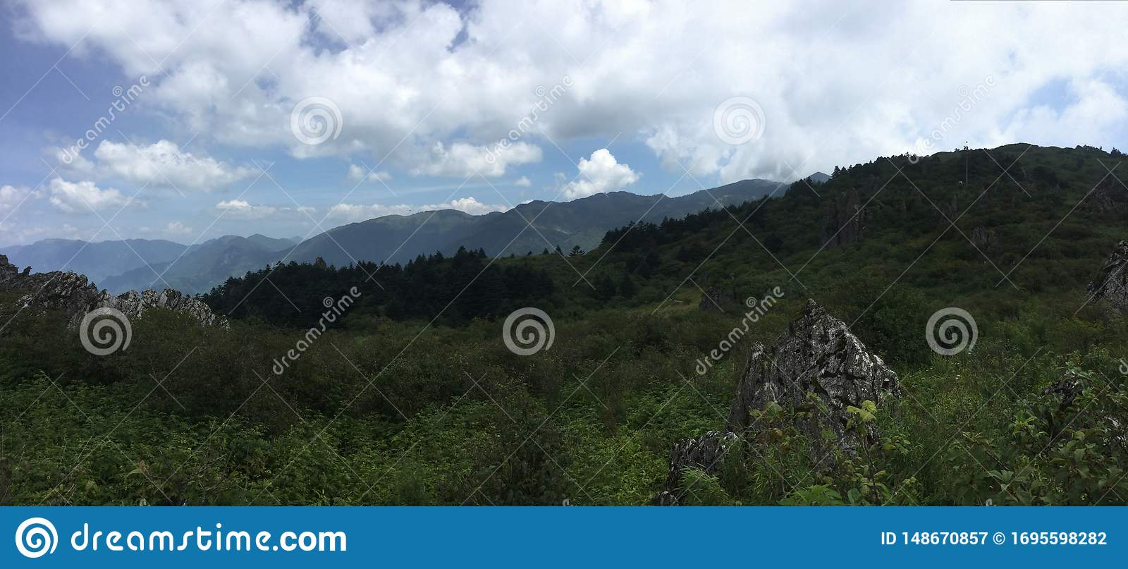 Blue sky, empty mountains, mountains in the distance, green, and many white clouds in the sky