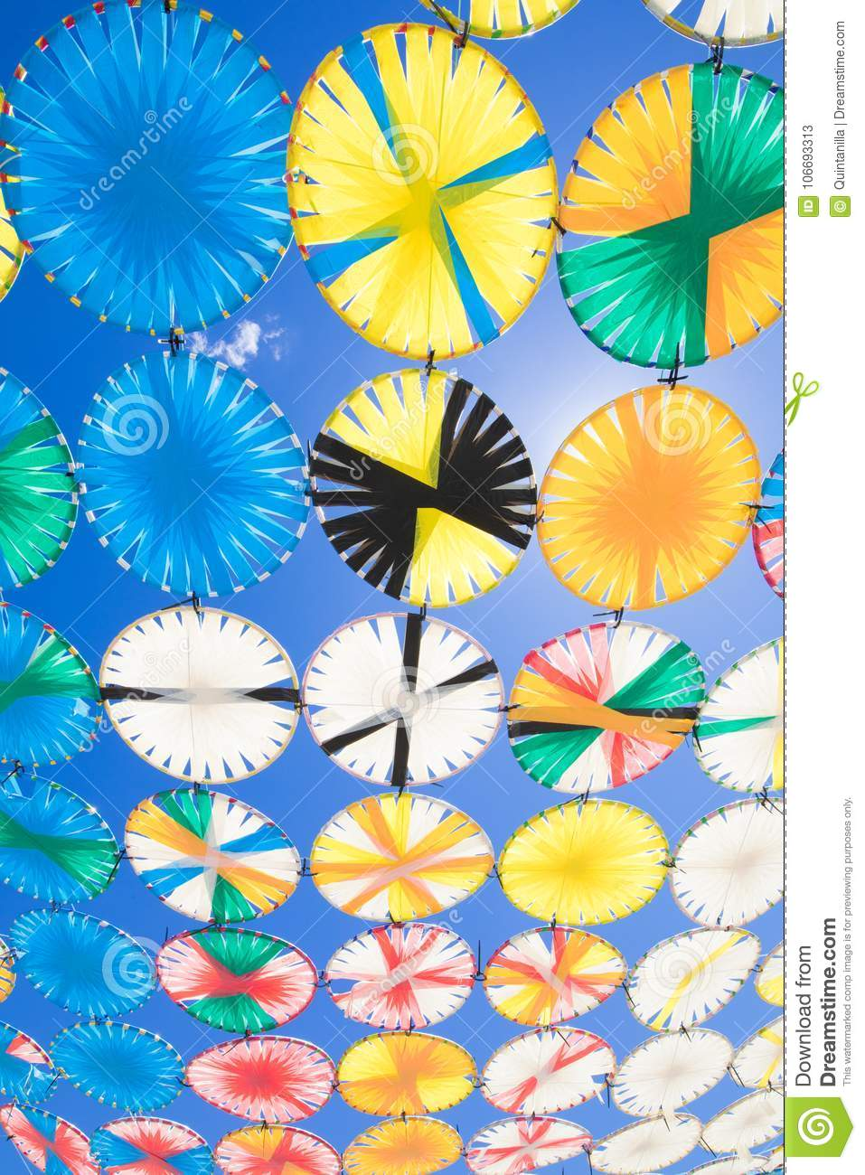 Sunshade multicolored circles row in blue sky vertical