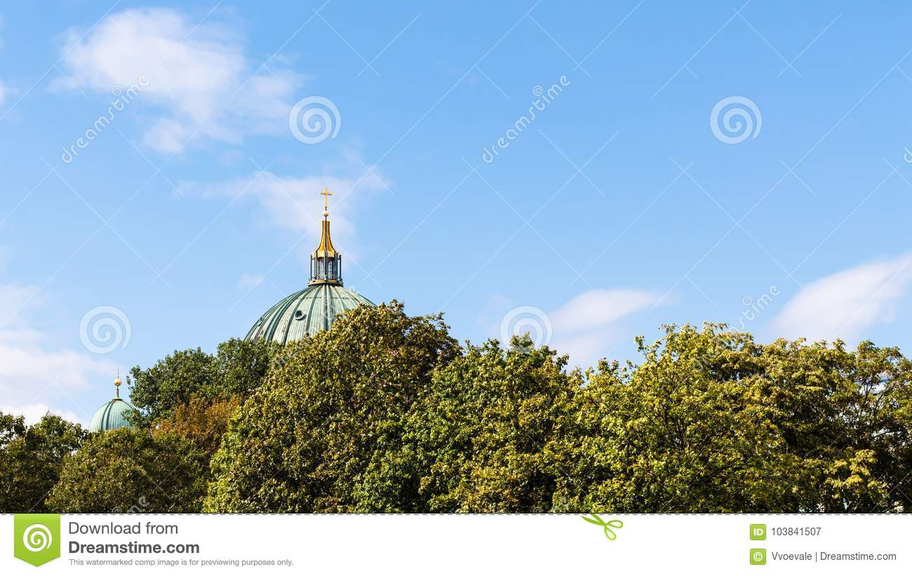Blue sky over green foliage and dome of Cathedral