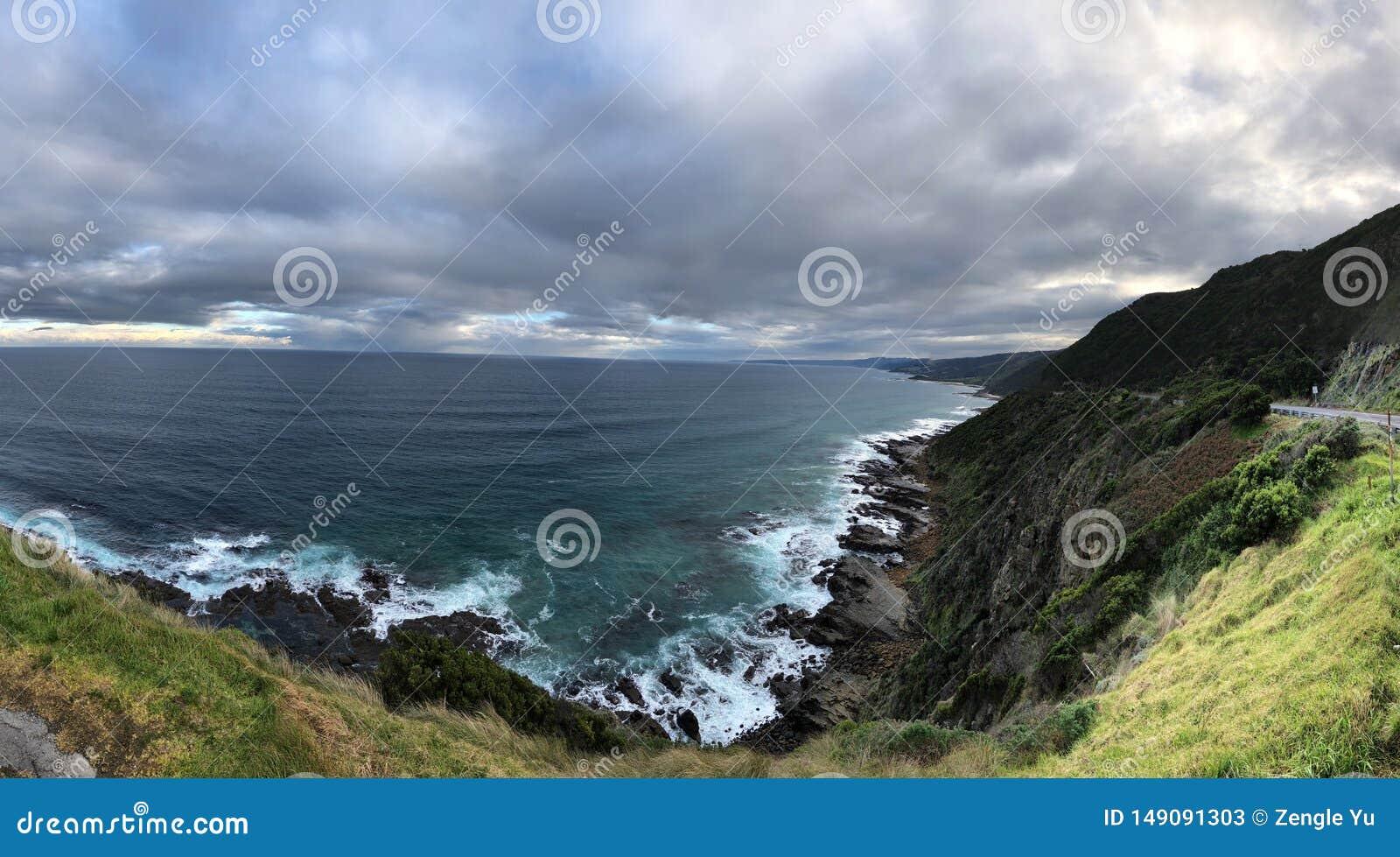 Blue sky, white surf, rocky coast, white clouds