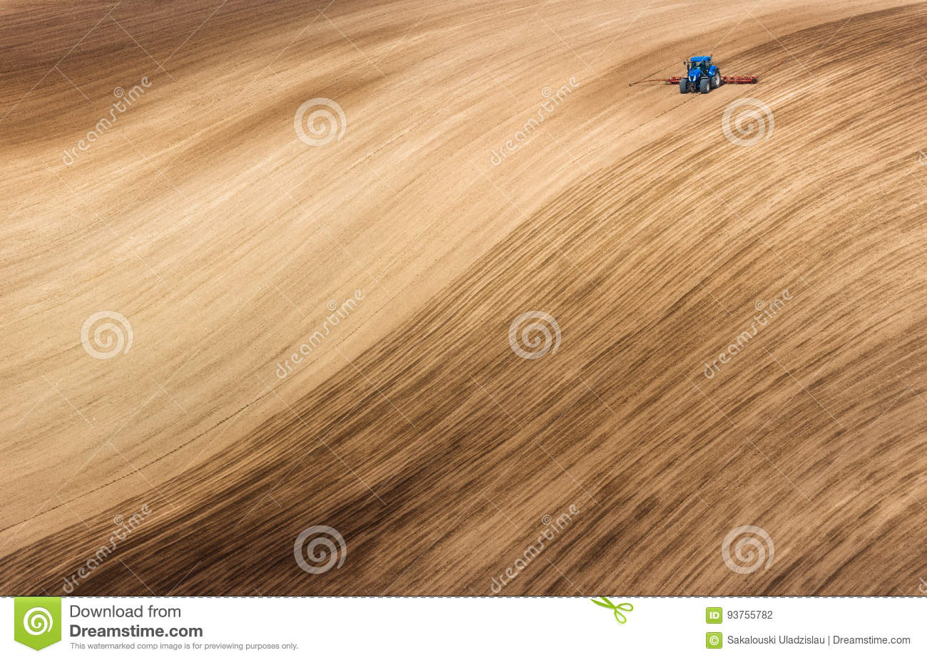 Blue Small Tractor Ploughing Brown Wavy Field. Scenic View Of Farming Tractor Which Plowing Spring Field.