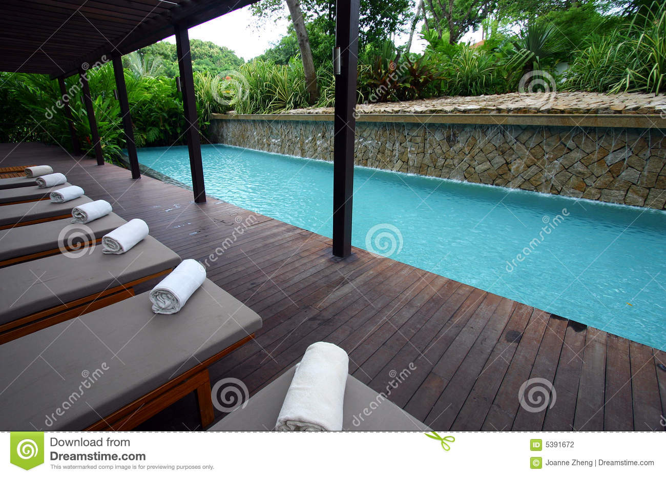 Blue spa resort poolside chaise lounges