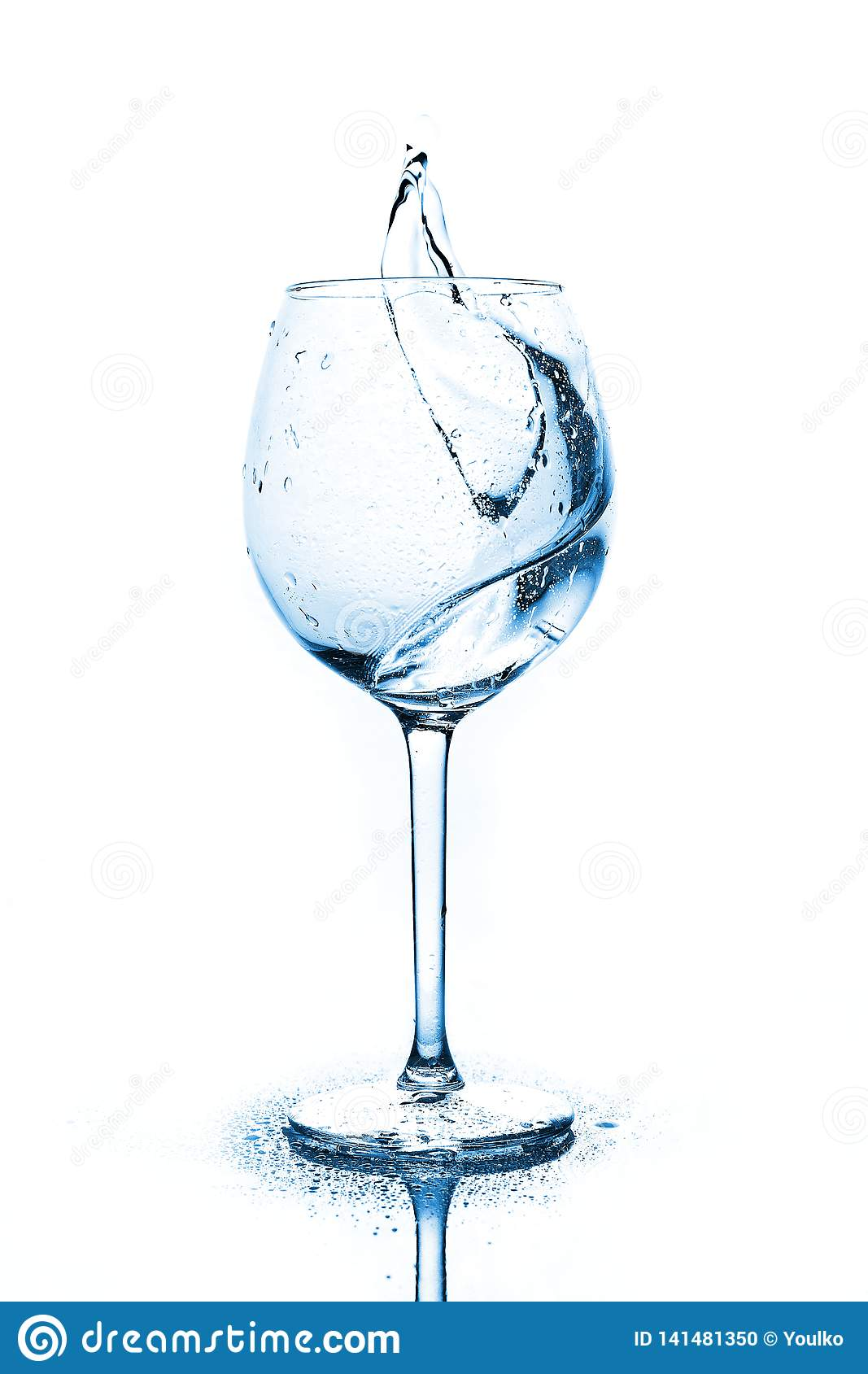 Blue splashes of clean water in the wine glass. A spray of water. Drinking water