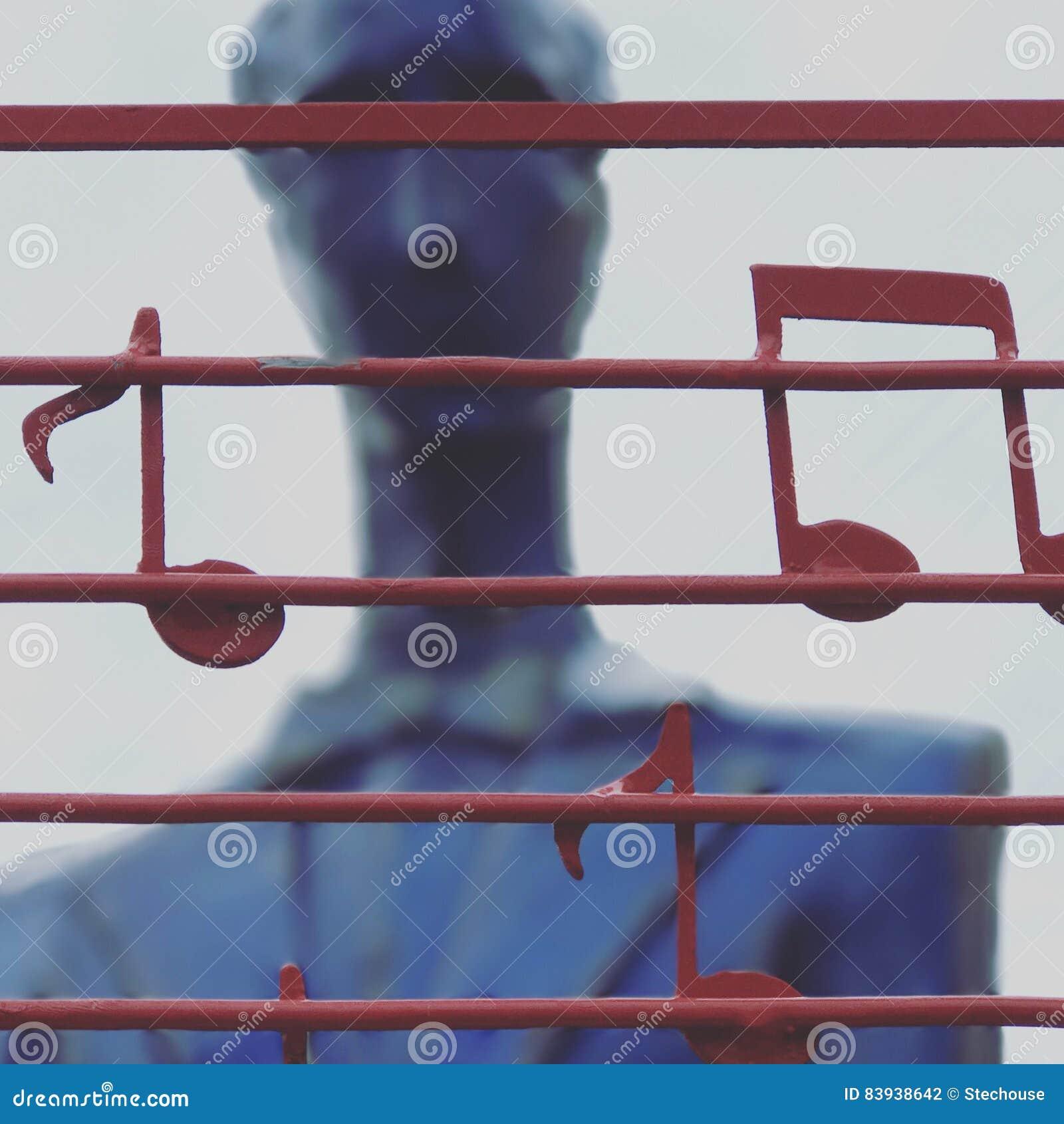 A blue statue plays an instrument