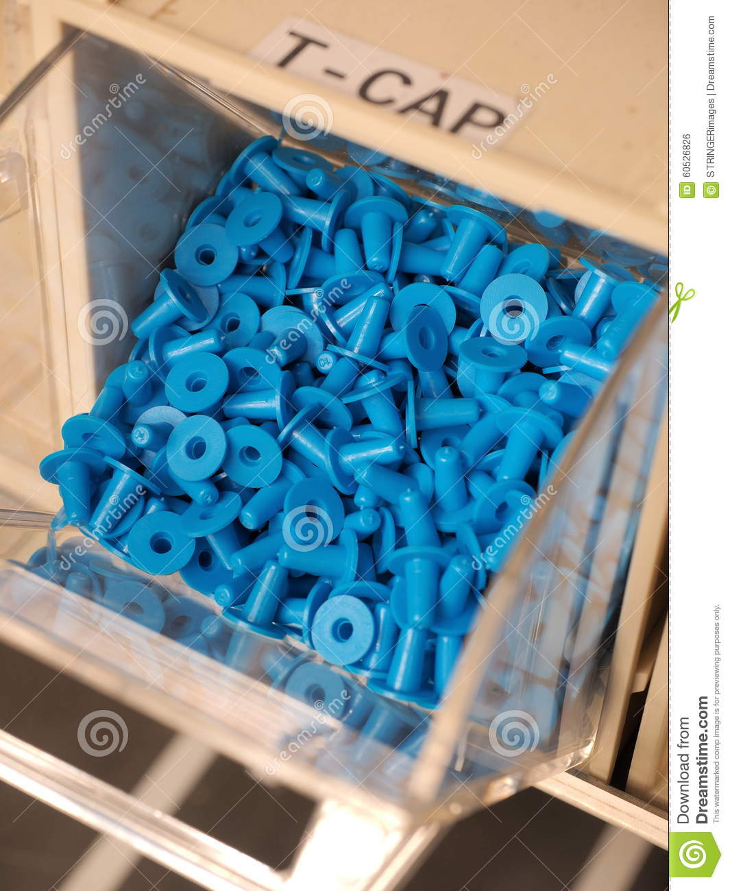 Blue T Shaped Plastic Plugs In A Storage Organizer Stock