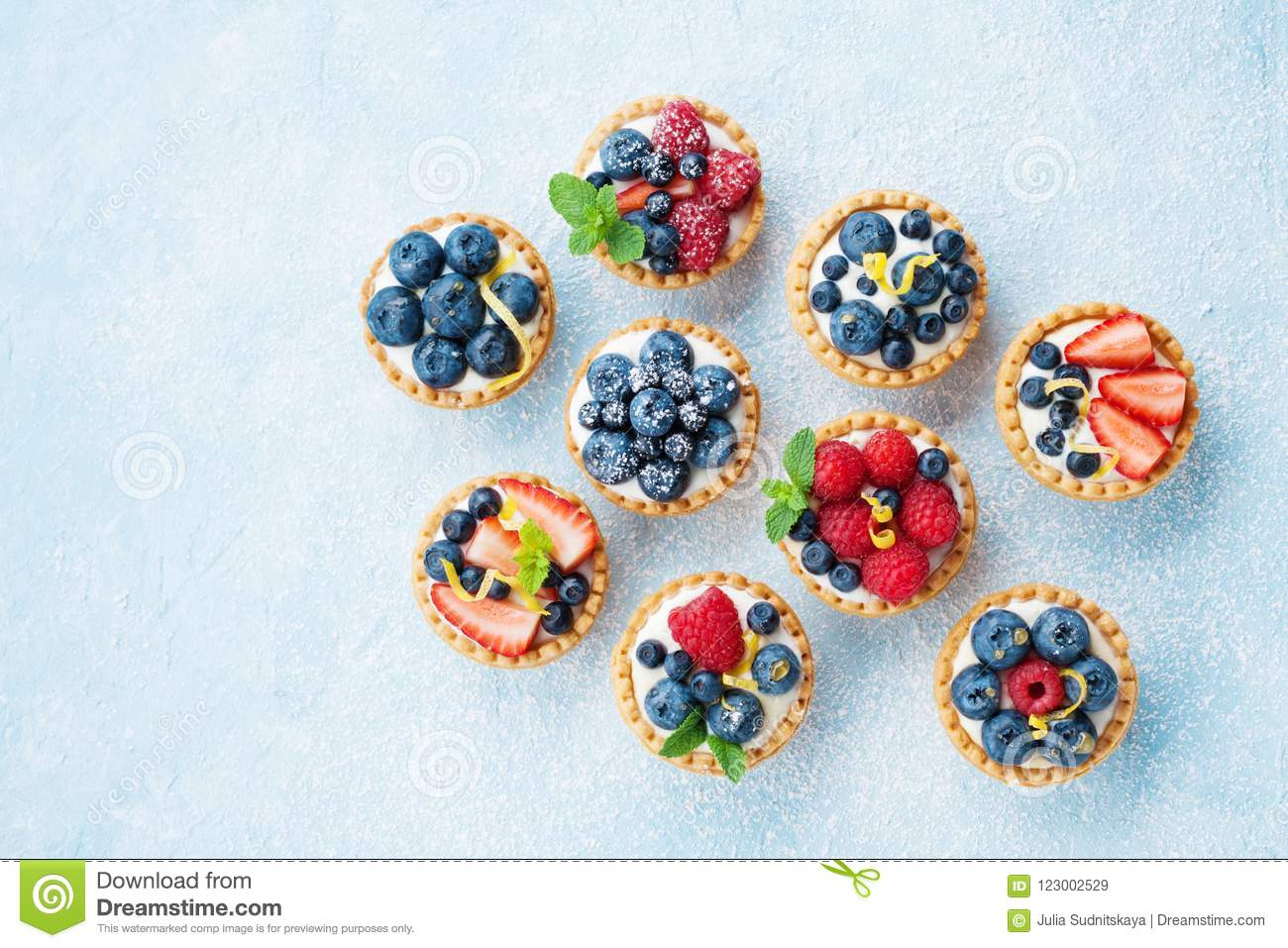 Blue table decorated of sugar powder with variety berry tartlets or cake top view. Tasty pastry desserts.