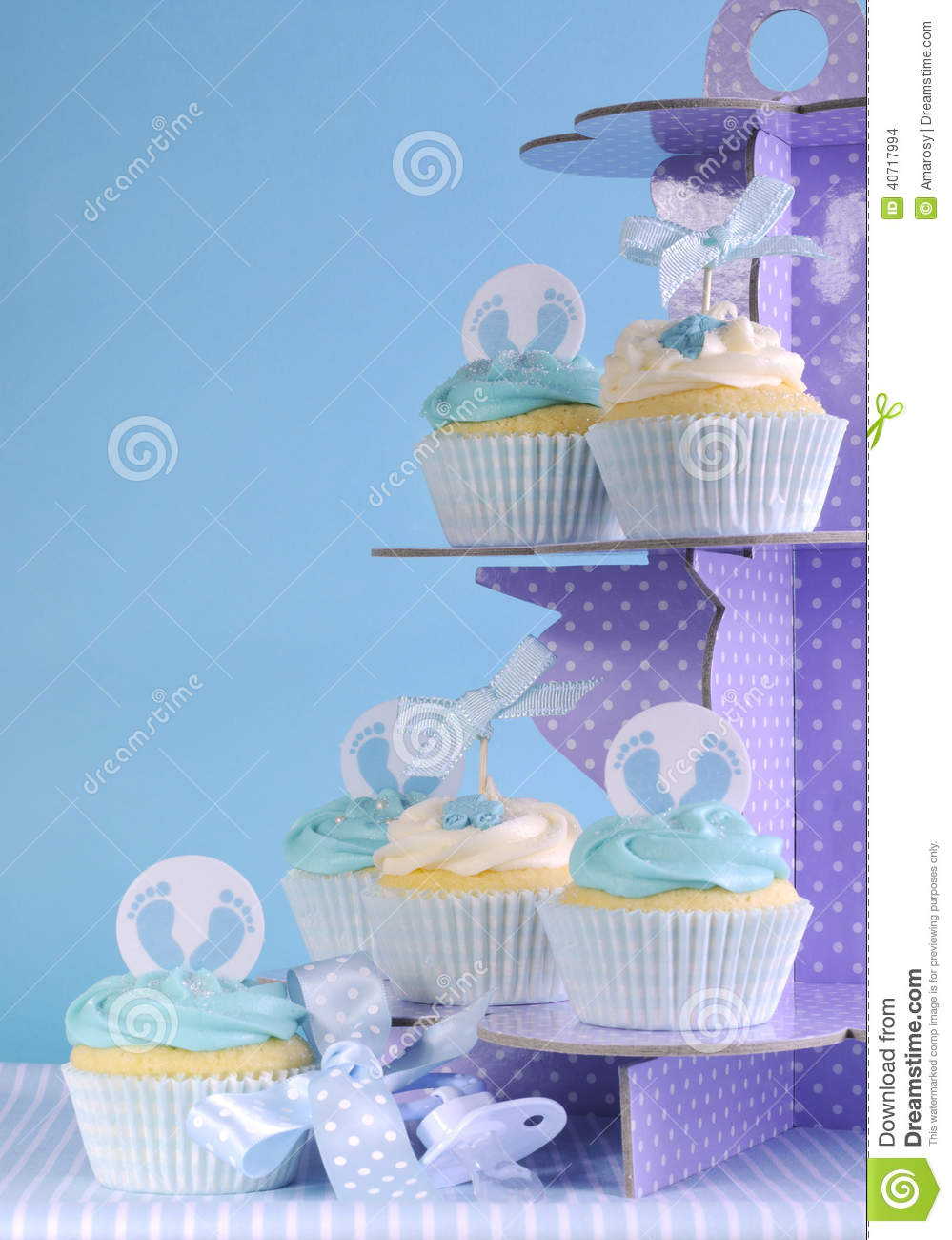 blue theme baby boy cupcakes on purple polka dot cupcake stand stock