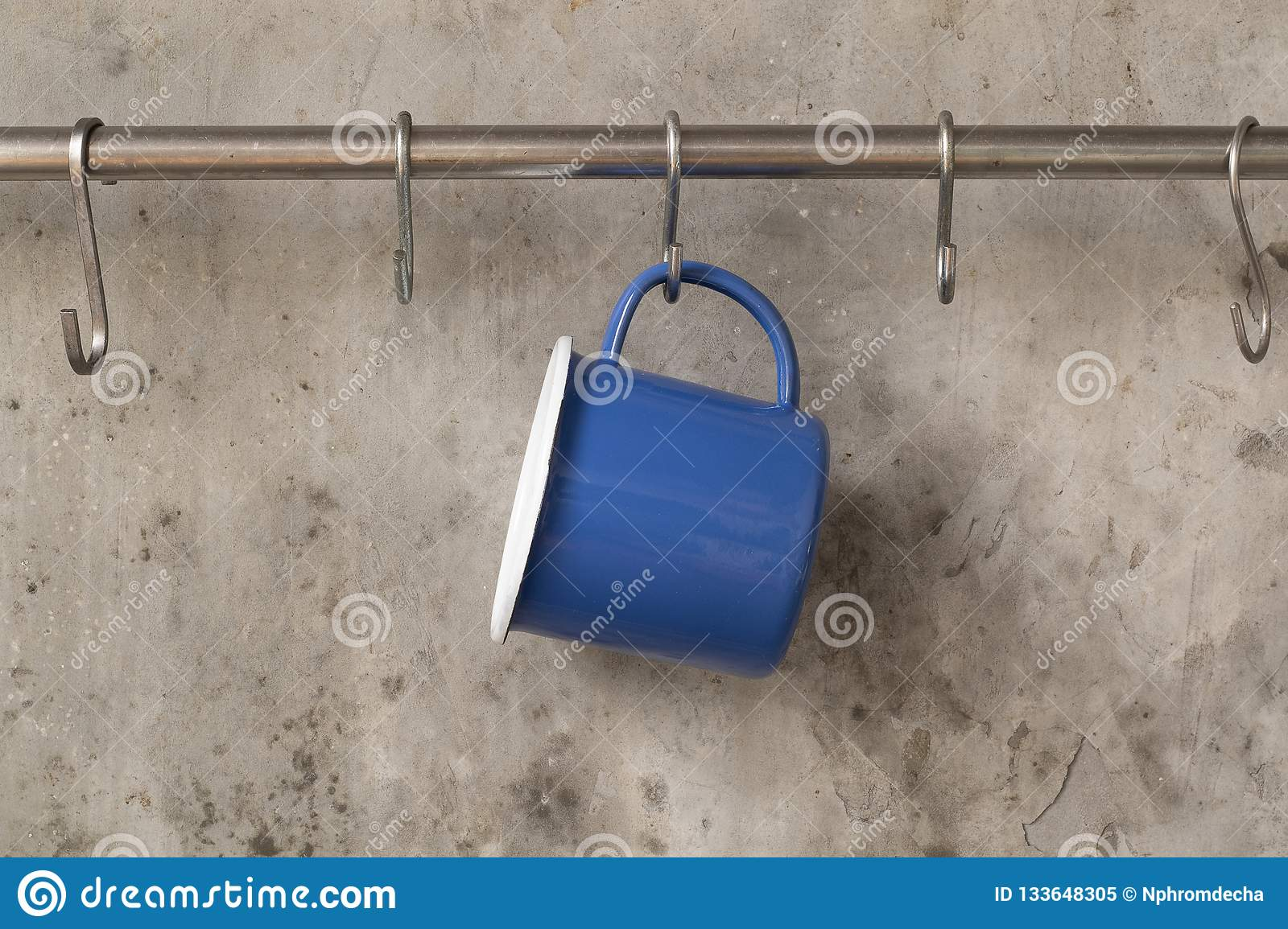 Blue tin cup hanging on stainless rail on cement wall background