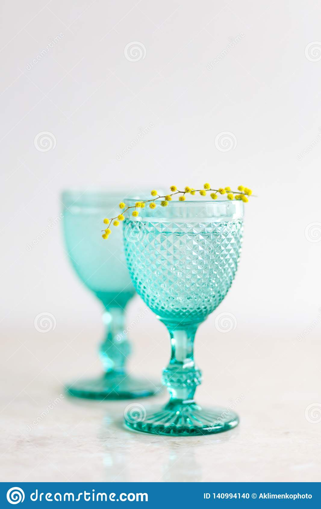 Blue Vintage Goblets and yellow mimosa flowers. Wineglasses on whight background