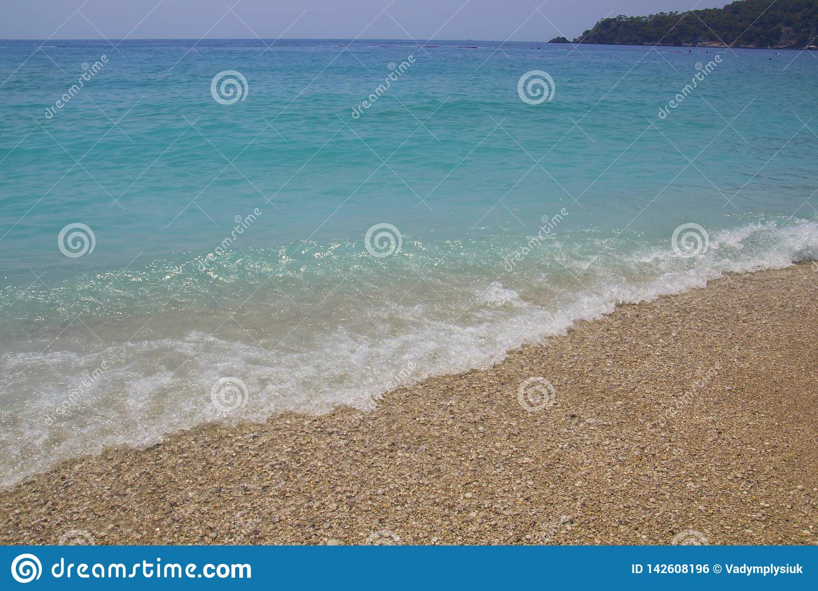 Blue water with sea foam. Small waves are coming to the shore. Turquoise water with white pebbles on the beach. Sea line meets the