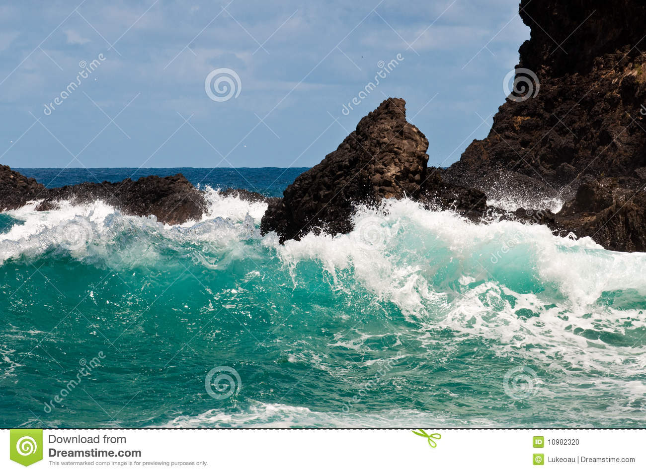 Large blue ocean waves crashing on natural rock formations, with a ...
