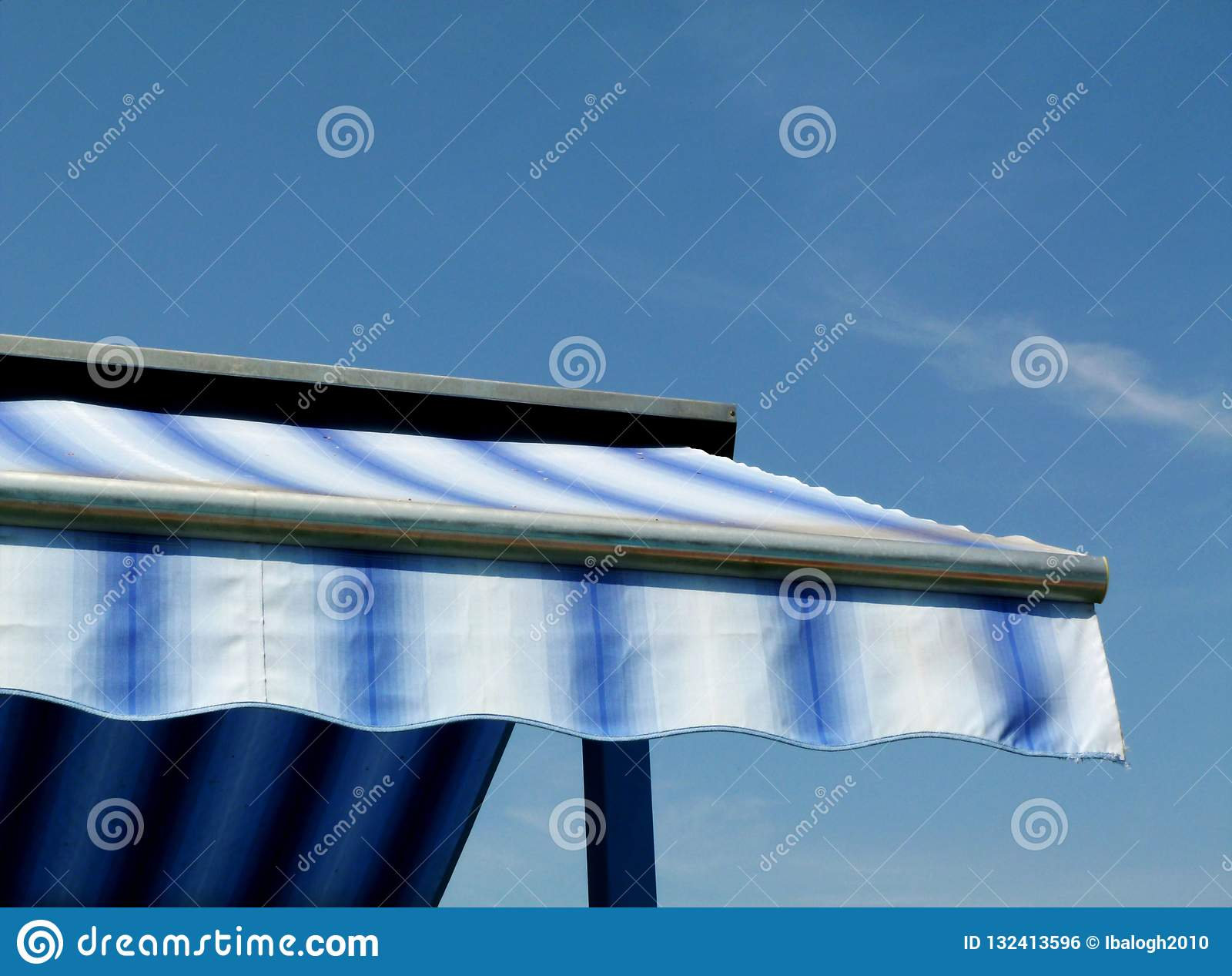 Blue and white canvas awning under blue sky