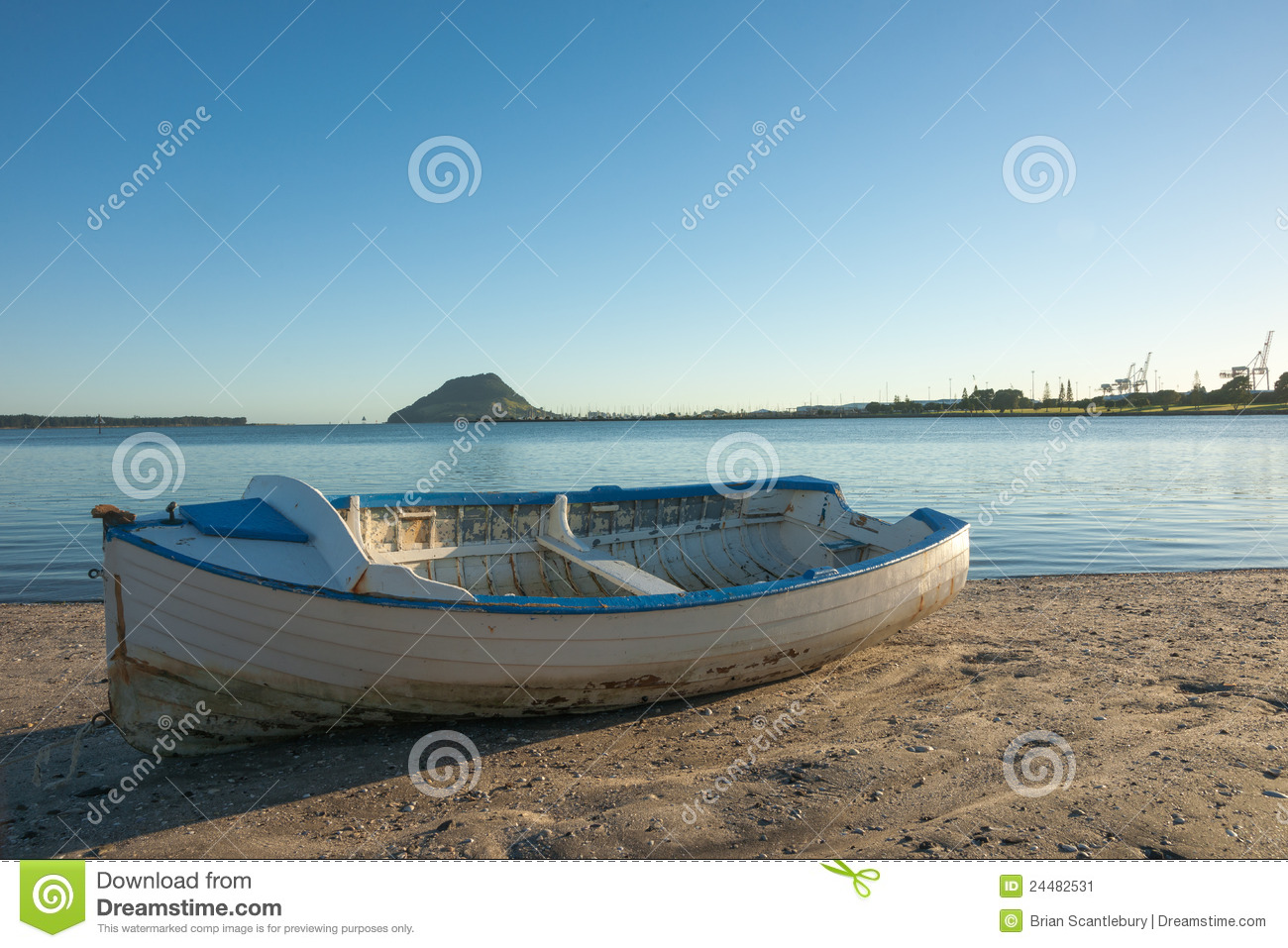 Blue and white clinker boat sits on beach with Mount Maunganui on ...