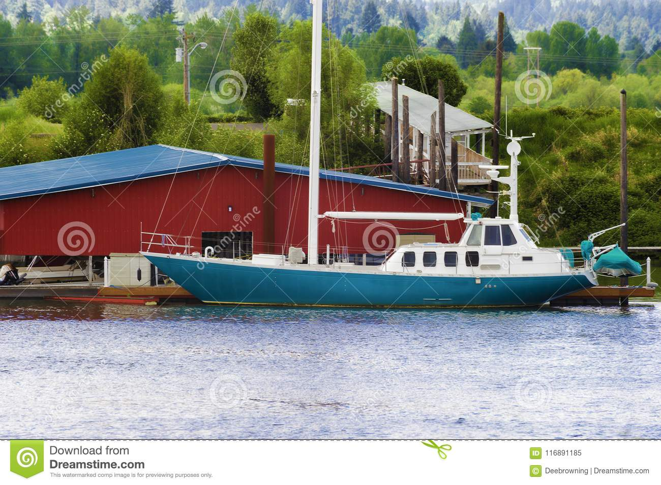 Blue and white sailboat docked on the Willamette River in Oregon