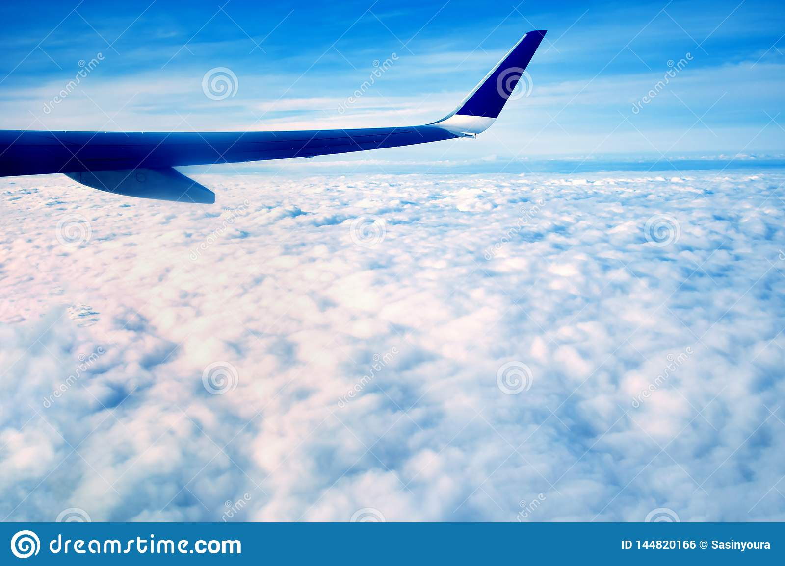 The blue wing of a large airplane, flying over the white morning clouds, at high altitude above the ground, against the blue sky
