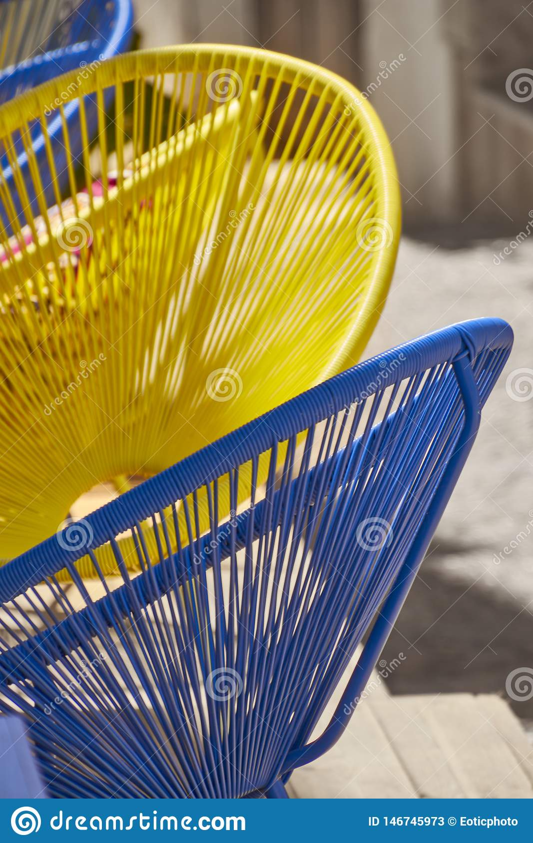 Blue and yellow chairs in sunny street