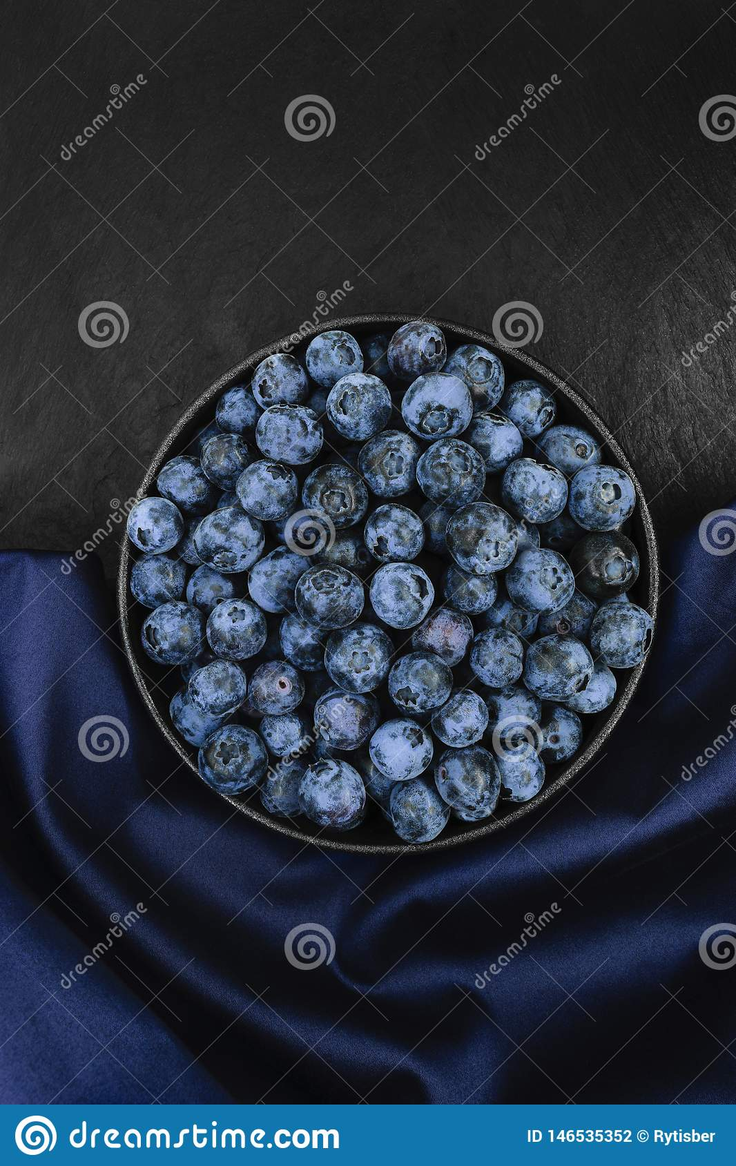 Blueberries on blue fabric and black stone background