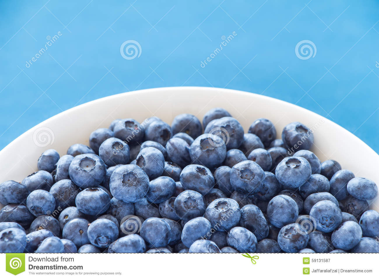 Blueberries In White Bowl On Colorful Blue Backround Stock ...