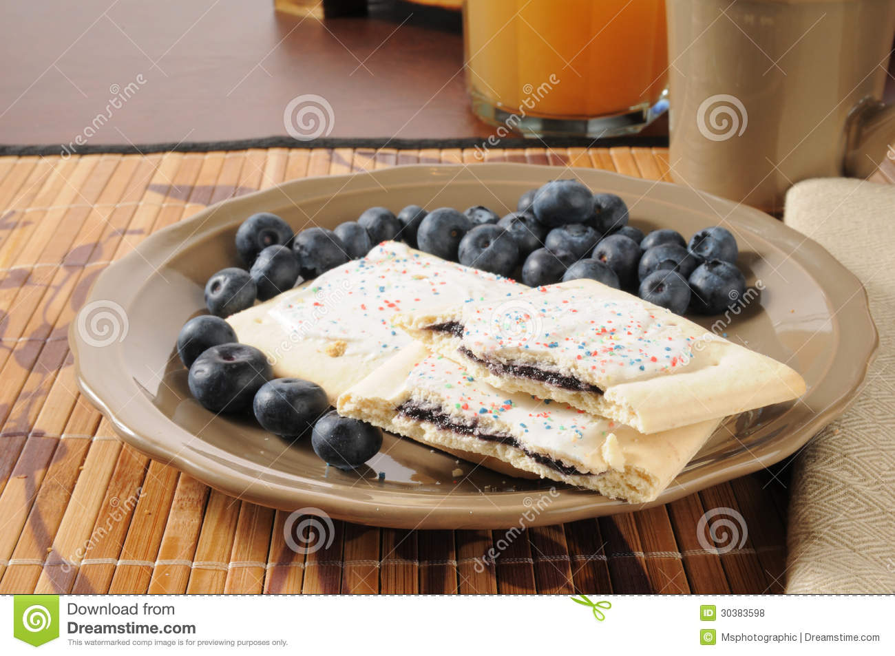 Toaster tarts with fresh blueberries and apple juice.